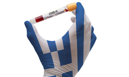 A COVID-labeled test tube held by hand with Greek flag colors.